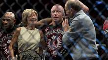 Georges St-Pierre celebrates with his parents after defeating Carlos Condit in their UFC welterweight title fight Sunday, November 18, 2012 in Montreal. A relentless St-Pierre celebrated his comeback by winning a five-round decision over Condit to unify the welterweight title in a bloody battle at UFC 154. (Ryan Remiorz/THE CANADIAN PRESS)