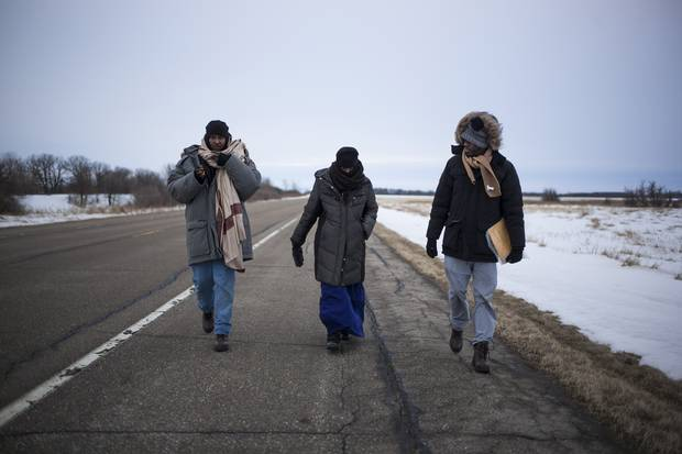 Abdullahi Warsame, Lul Abdi Ali and Delmar Xasan, all refugees from Somalia, walk north toward Canada in Noyes, Minn., on Feb. 19, 2017.