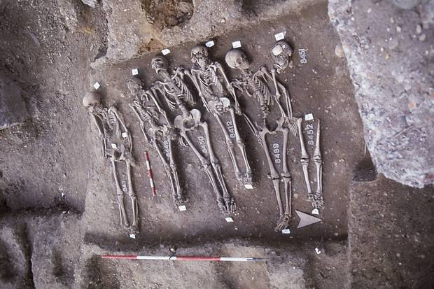 Five skeletons are unearthed from England's East Smithfield site, a 'plague pit' used in the 14th century as a mass grave for victims of the Black Death.
