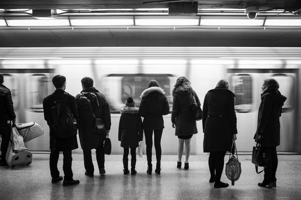 Riders wait for an arriving northbound train at Queen subway station.