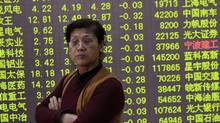 An investor stands in front of an electronic board showing stock information filled with green figures indicating falling prices at a brokerage house in Hangzhou, Zhejiang province Dec. 26, 2013. (REUTERS)