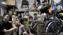 Migrant workers watch Olympic matches on TV in a room at Huangbeiling Village in Shenzhen of south China's Guangdong province Aug. 10, 2008. (Chen Yihuai/ColorChinaPhoto/Chen Yihuai/ColorChinaPhoto)