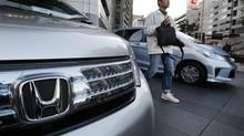 A man walks by Honda vehicles displayed in front of Honda Motor Co. headquarters in Tokyo Monday, Oct. 29, 2012. (Koji Sasahara/AP)