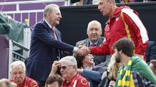 International Olympic Committee president Jacques Rogge, top left, greets an Olympic official as he arrives to watch the men's beach volleyball semi-final matches at Horse Guards Parade during the London 2012 Olympic Games August 7, 2012. (SUZANNE PLUNKETT/REUTERS)