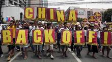 Protesters shout slogans as they march towards the Chinese consulate during a rally Friday, May 11, 2012 in Manila's financial district of Makati, Philippines. (Pat Roque/AP)