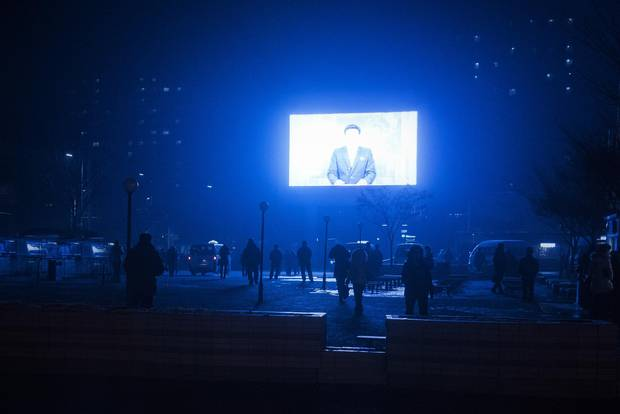 State news beams out across a public square on a subzero December night. Though photography generally isn't allowed outside the specific sights vetted for foreign visitors, in practice restrictions are somewhat looser, with enforcement at the guides' discretion.