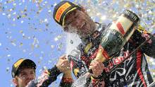 In this file photo, Red Bull Formula One World Champion Sebastian Vettel (L) sprays champagne on teammate Mark Webber the Brazilian F1 Grand Prix (2011) (Nacho Doce/Reuters)
