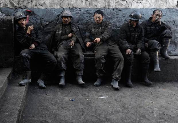 Miners smoke during a break at a coal mine in Changzhi, Shanxi province November 25, 2009. China, the world's top emitter of greenhouse gases, is aiming for many more years of rapid growth fuelled by coal as its main energy source. Picture taken November 25, 2009.