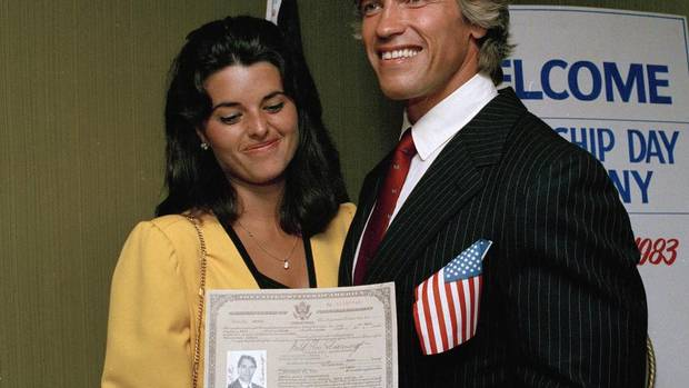 In this Sept. 16, 1983 photo, actor and bodybuilder Arnold Schwarzenegger shows off his new U.S. citizenship papers as Maria Shriver looks on at the Shrine Auditorium in Hollywood, Calif. (Wally Fong/AP)