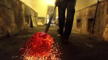 BBQ cooker Terry Blow carries red hot coals into the pit house at Scott's BBQ in Hemingway, South Carolina, June 20, 2012. Picture taken June 20, 2012. (RANDALL HILL/REUTERS)