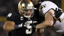 Notre Dame Fighting Irish linebacker Manti Te'o gets past Wake Forest Demon Deacons guard Dylan Intemann during the second half of their NCAA college football game in South Bend, Indiana, in this November 17, 2012 file photo. (JEFF HAYNES/REUTERS)