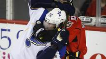 St. Louis Blues' David Backes, left, gets grabbed in a choke hold by Calgary Flames' Mark Giordano during first period NHL hockey action in Calgary, Alta., Thursday, Jan. 9, 2014. (Jeff McIntosh/THE CANADIAN PRESS)