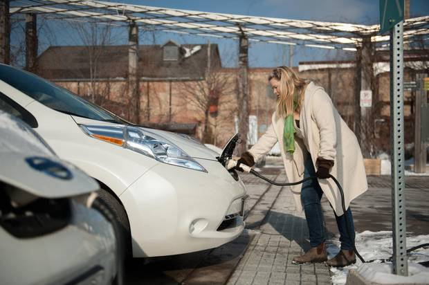 Julia Schindeler charges her electric car, a Nissan Leaf, at a charging station at the Evergreen Brickworks in Toronto.