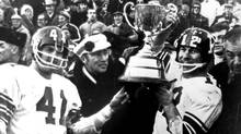 Ottawa Rough Riders' Russ Jackson (right) holds the Grey Cup as Prime Minister Trudeau (centre) and team mate Ken Lehmann looks on in Montreal on Nov. 30, 1969. Ottawa won the game 29-11 over Saskatchwan. (CP Photo Archive)