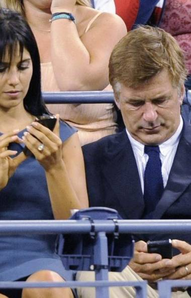 Newlyweds Alec Baldwin and wife Hilaria Thomas put on one of those phony public displays of intimacy that make people so cynical about celebrity marriage at the U.S. Open tennis tournament in New York on Monday. (Reuters)