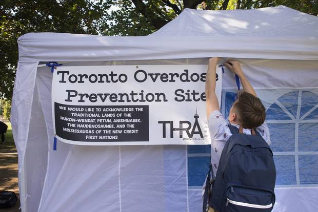 Volunteer Shawn Craig places a sign for a pop-up supervised drug-use site at Moss Park in downtown Toronto on Sept 13 2017.