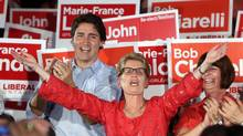 Ontario Liberal leader Kathleen Wynne waves to supporters as Federal Liberal leader Justin Trudeau looks on during a Ontario Liberal campaign stop in Ottawa, Wednesday June 4, 2014. (FRED CHARTRAND/THE CANADIAN PRESS)