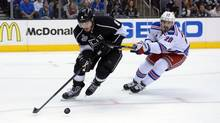 Los Angeles Kings defenseman Drew Doughty (8) reaches for the puck against New York Rangers left wing Chris Kreider (20) in the second period during game one of the 2014 Stanley Cup Final at Staples Center. (© USA Today Sports / Reuters)