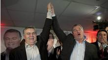 Quebec Liberal candidate Damien Arsenault, left, gets his hand raised in victory by Health Minister Yves Bolduc after winning a by-election in the riding of Bonaventure. (Jacques Boissinot/Jacques Boissinot/THE CANADIAN PRESS)