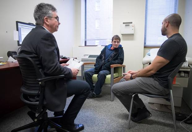 Dr. Mark McLean, left, and addictions registered nurse Sherif Amara, right, talk with patient Daniel Lagrois at St. Paul's Hospital, in Vancouver.