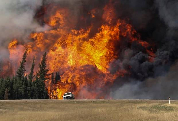 Smoke and flames from the wildfires erupt behind a car on the highway near Fort McMurray, May 7, 2016.