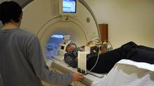 Research engineer Fred Tam prepares a volunteer while demonstrating the driving simulator set up with an fMRI at Sunnybrook Hospital in Toronto. (Fred Lum/The Globe and Mail)