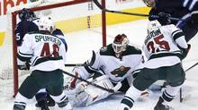Minnesota Wild's goaltender Niklas Backstrom (32) gets a leg on Winnipeg Jets' Mark Scheifele's (55) shot as the Jets' Matt Halischuk (15) and Wild's goaltender Darcy Kuemper (35) and Jared Spurgeon (46) look for the rebound during first period NHL action in Winnipeg on Saturday, November 23, 2013. (JOHN WOODS/THE CANADIAN PRESS)