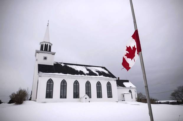 A tattered Canadian flag flies at half-mast for the combined funerals of Lionel Desmond and his mother, Brenda Desmond, at St. Peter's Church on Jan. 11, 2017.