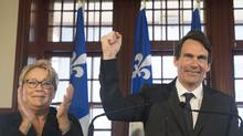 Quebec Premier Pauline Marois looks on as Pierre Karl Péladeau gestures during a press conference. (GRAHAM HUGHES/THE CANADIAN PRESS)