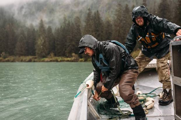 Two salmon fisherman gather their net from the river in River's Inlet, B.C.