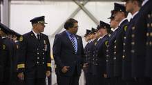 Calgary deputy fire chief Tom Sampson, left, and Mayor Naheed Nenshi stop and chat with a new firefighter as they inspect the new recruits at a graduation ceremony on July 18, 2013. The new firefighters had been pulled away from training to battle the city's recent floods. (TODD KOROL FOR THE GLOBE AND MAIL)