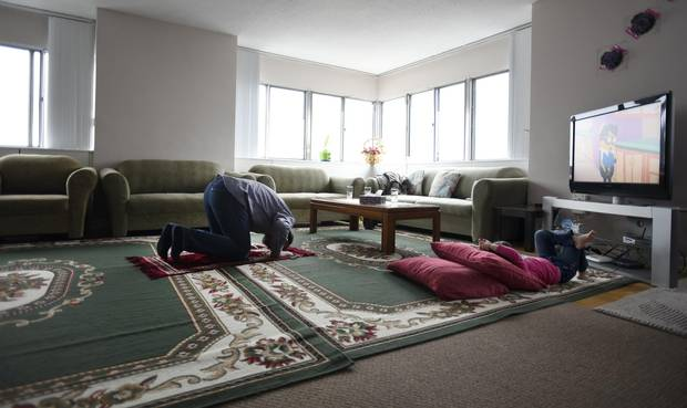 Unable to go to his mosque for prayer service, Ahmad Al Rasoul prays in his family's apartment while daughter Sava, 3, watches TV.
