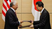 Malaysia's Prime Minister Najib Razak and Japanese Prime Minister Yukio Hatoyama exchanges documents during a signing ceremony at the latter's official residence in Tokyo April 19, 2010. (YURIKO NAKAO)