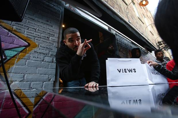 Drake poses for photos as he hands out T-shirts at a pop up shop in Toronto to promote his new album on Sunday.