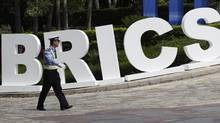 A traffic policeman walks past a signage decoration for BRICS Summit outside the Sheraton Hotel, the venue of BRICS (Brazil, Russia, India, China and South Africa) Summit in Sanya, China's Hainan province, April 13, 2011. (JASON LEE)