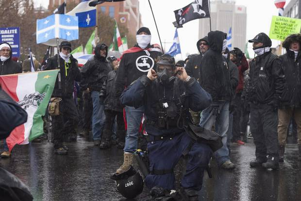 Nov. 25, 2017: A police officer puts on his gas mask in front of members of the right-wing group Storm Alliance at a Quebec City demonstration where antifacists and extreme right groups faced one another. Organizations like Storm Alliance and La Meute have tried to stoke racial tensions in Canada and resentment of immigrants.