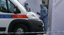 Police forensics officers investigate a crime scene where one man was killed in Woolwich, southeast London May 22, 2013. British Prime Minister David Cameron has called a meeting of his government's emergency Cobra security committee after the killing of a man in south London, his office said on Wednesday. (STEFAN WERMUTH/Reuters)