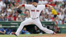 In this July 20, 2014, file photo, Boston Red Sox's Jon Lester pitches during the eighth inning of a baseball game against the Kansas City Royals, in Boston. A person with knowledge of the trade says the Athletics have won the Jon Lester sweepstakes, acquiring the left-hander along with outfielder Jonny Gomes from the Red Sox for slugging outfielder Yoenis Cespedes before Thursday's, July 31, 2014, trade deadline. The person spoke on condition of anonymity because neither club announced the deal. (Michael Dwyer/AP)
