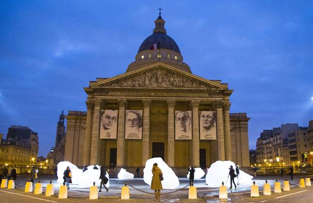 Visitors watch ice blocks harvested from Greenland, part of the sculpture Ice Watch by Danish artist Olafur Eliasson, in front of the Pantheon in Paris on Dec. 3 2015.
