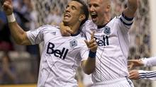 In this file photo, Vancouver Whitecaps FC Camilo Sanvezzo, left, celebrates his goal with teammate Kenny Miller during the first half against Chivas USA during first half of MLS soccer action in Vancouver, Wednesday, June, 19, 2013. The Whitecaps won 3-1. (JONATHAN HAYWARD/THE CANADIAN PRESS)