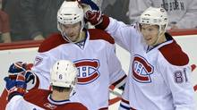 Montreal Canadiens' Benoit Pouliot celebrates with Jaroslav Spacek (6) and Lars Eller, right, after Pouliot scored during the second period of an NHL hockey game against the New Jersey Devils, Thursday, Dec. 2, 2010, in Newark, N.J. The Canadiens won 5-1. (Bill Kostroun)