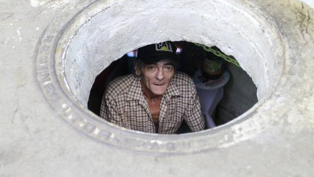 Miguel Restrepo, 62, looks up from his sewer home in Medellin December 4, 2012. The former drug addict has been living in an abandoned sewer with his wife, Maria Garcia, and dog, Blackie, for 22 years. (ALBEIRO LOPERA/REUTERS)