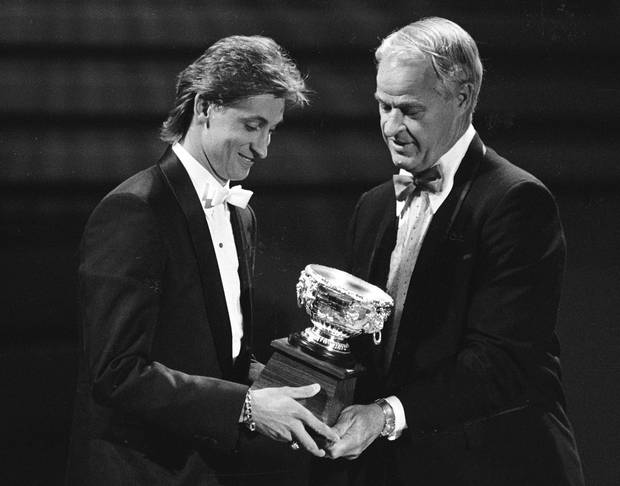 Edmonton Oilers Wayne Gretzky (L) receives the Art Ross Trophy from hall of fame player Gordie Howe during the NHL Awards in Toronto, Ontario, Canada on June 10, 1987.