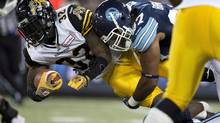Toronto Argonauts defensive lineman Ivan Brown (right) tackles Hamilton Tiger-Cats running back C.J. Gable during first half CFL action in Toronto on Friday October 4, 2013. (Frank Gunn/THE CANADIAN PRESS)