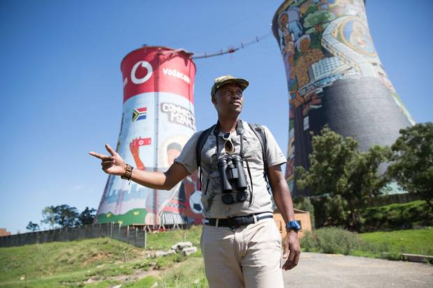 Raymond Rampolokeng shows tourists some of the 68 different bird species that he has found in the wetlands and hills of the sprawling community of Soweto.