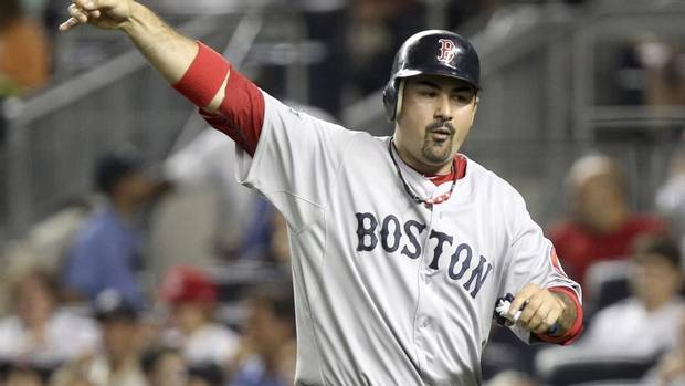 In this July 29, 2012 file photo, Boston Red Sox's Adrian Gonzalez gestures after scoring during a game against the New York Yankees at Yankee Stadium in New York. The Red Sox have traded Gonzalez, pitcher Josh Beckett and outfielder Carl Crawford to the Los Angeles Dodgers in a nine-player deal. The trade was officially announced on Saturday, Aug. 25, 2012. The nine-player swap is the largest for the Dodgers since they moved to Los Angeles. (Seth Wenig/AP)