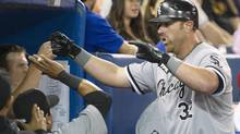 Chicago White Sox's Adam Dunn (R) is congratulated by teammates after hitting a three run home run against the Toronto Blue Jays in the seventh inning of their American League baseball game in Toronto August 15, 2012. (FRED THORNHILL/REUTERS)