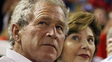 Former U.S. president George W. Bush and his wife, Laura, take in a Major League Basebeall playoff game in Arlington, Tex., on Oct. 8, 2011. (HANS DERYK/REUTERS)