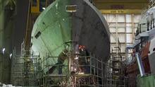 Technicians work on a hull at Halifax Shipyard in Halifax on March 7, 2013. (ANDREW VAUGHAN/THE CANADIAN PRESS)