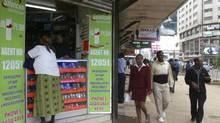 Pedestrians walk past an M-PESA mobile banking shop in downtown Nairobi, Kenya, on May 12, 2009. (NOOR KHAMIS/REUTERS)